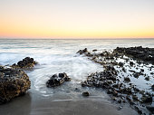 Sunset with nightfall light and the moon in the sky, on the beach and rocky coast of the Cabo de Gata with formations of volcanic rock. Cabo de Gata - Nijar Natural Park, Monsul creek, Biosphere Reserve, Almeria,  Andalusia, Spain