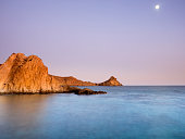 Sunset  with nightfall light and the moon in the sky, on the beach and rocky coast of the Cabo de Gata with formations of volcanic rock. Cabo de Gata - Nijar Natural Park, Punta Baja Biosphere Reserve, Almeria,  Andalusia, Spain