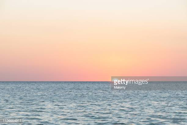 sunset with orange colored sky and horizon over the sea. - quintana roo stock pictures, royalty-free photos & images