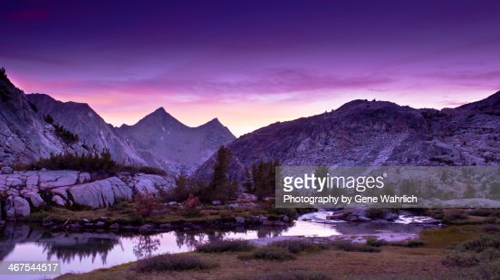 Sunset with purple sky, lake and mountains