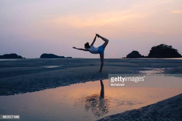 Sunset yoga on the sandy beach of Koh Lanta, Thailand