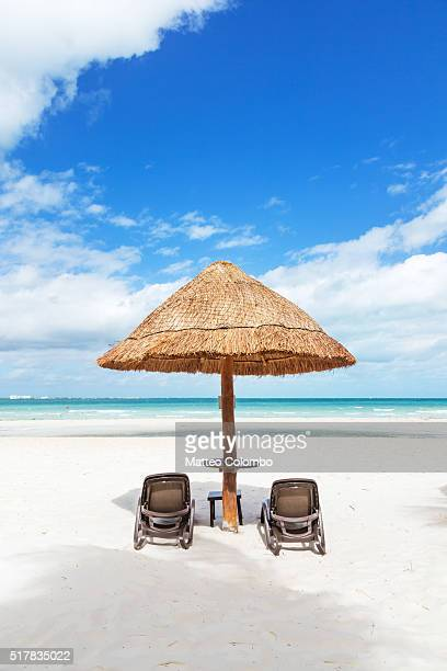 Sunshade and lounge chairs on sandy beach in the Caribbean, Cancun, Mexico