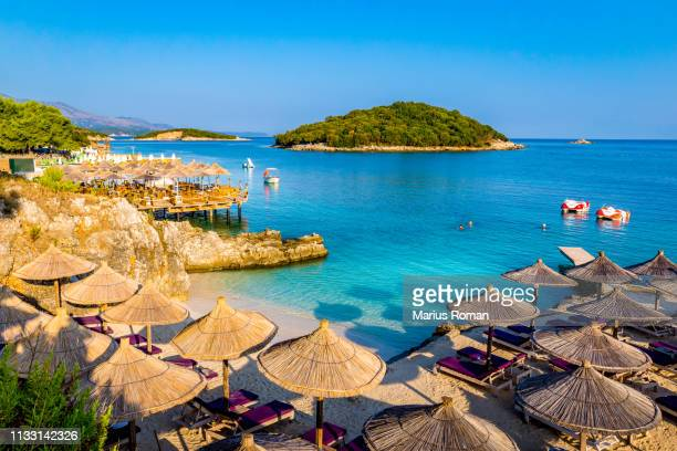 sunshade umbrellas, deckchairs and boats on the beautiful ksamil beach, vlore, ionian sea, albania, balkans, europe. - albania stock-fotos und bilder