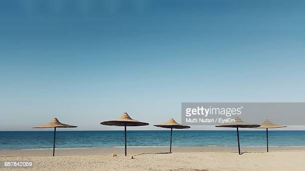 Sunshades At Beach Against Clear Sky