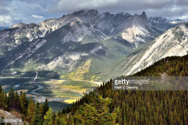 sunshine and cloud shadows across a mountainside. - sulphur mountain stock pictures, royalty-free photos & images