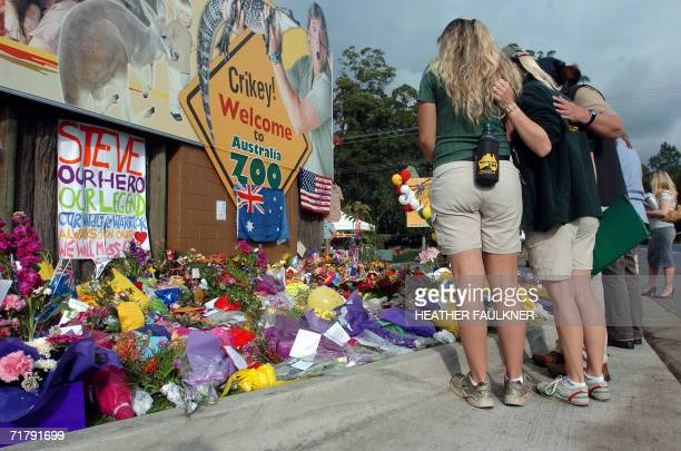 Sunshine Coast, AUSTRALIA: Staff members from Australia Zoo console each others as they observe the thousands of tributes and flowers from friends...