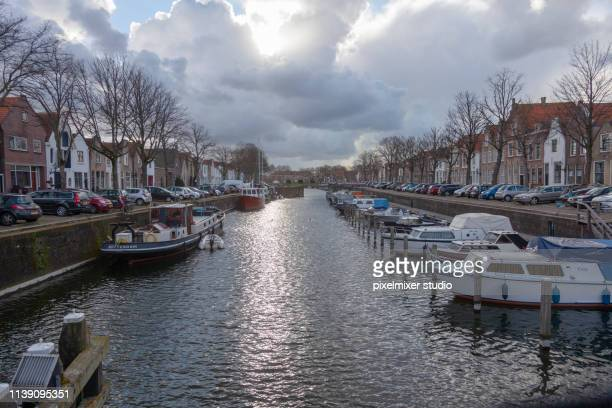Sunshines throut the clouds at Brille ,Netherlands , with boats at the deck,and trees all oner around