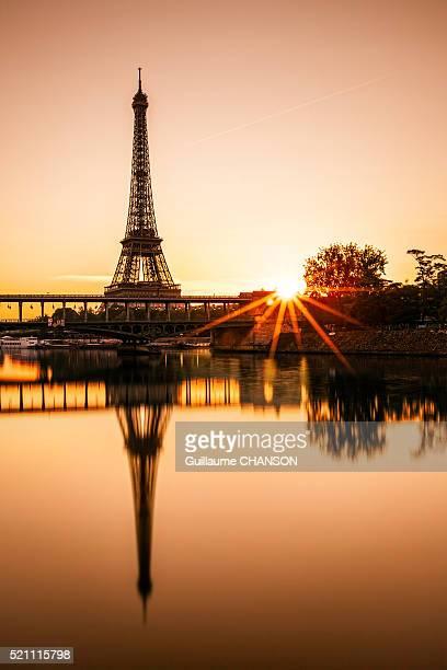 Sunstar at sunrise in front of Bir-Hakeim bridge and Eiffel Tower in Paris, France