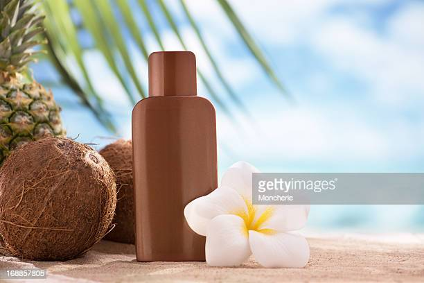 Suntan lotion, coconuts and plumeria flower with copy space