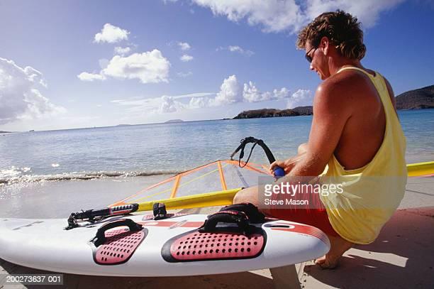 suntanned windsurfer sitting on beach - sin mangas fotografías e imágenes de stock