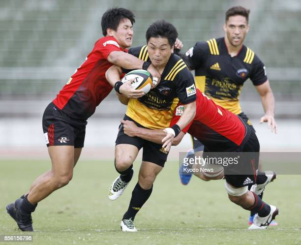 Suntory Sungoliath's Kosei Ono is tackled by NTT Docomo Red Hurricanes in the second half of a Japan Rugby Top League match in Kofu Yamanashi...