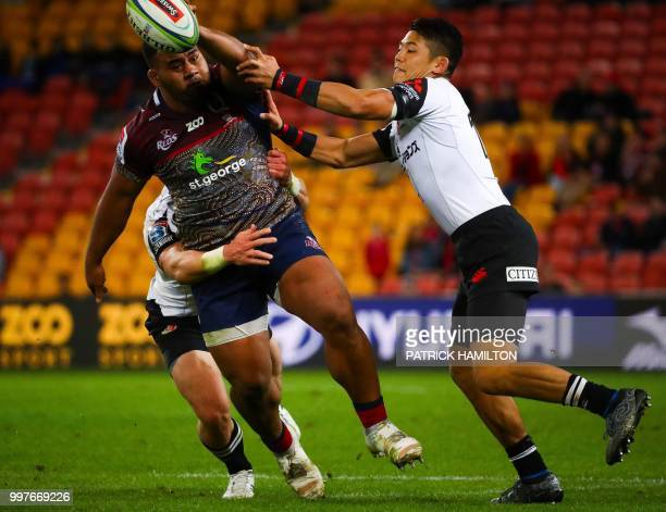 Sunwolves players Willie Britz and Yoshikazu Fujita tackle Reds player Taniela Tupou during the Super Rugby match between Australia's Queensland Reds...