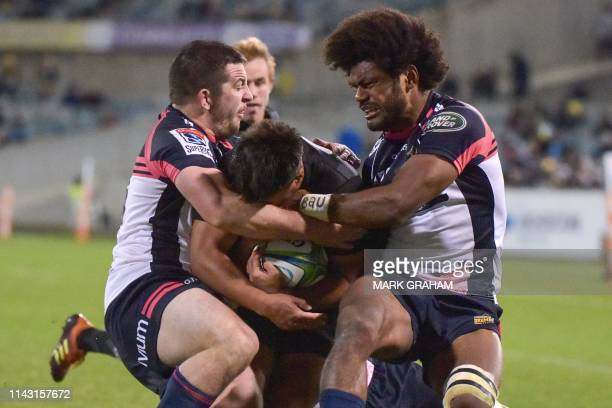 Sunwolves' Rahboni Warren-Vosayaco is tackled by Brumbies' Connal McInerney and Henry Speight during the Super Rugby match between the Australia's...