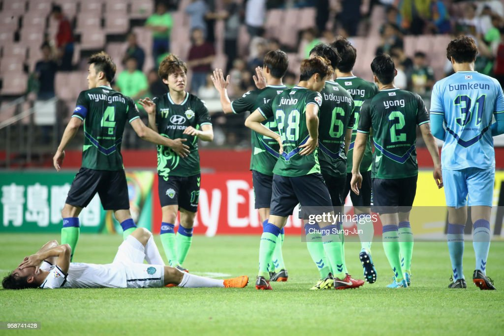 Supachok Sarachart of Buriram United shows dejection while Jeonbuk Hyundai Motors players celebrate their 2-0 victory and 4-3 aggregate win in the AFC Champions League Round of 16 second leg match between Jeonbuk Hyundai Motors and Buriram United at Jeonju World Cup Stadium on May 15, 2018 in Jeonju, South Korea.