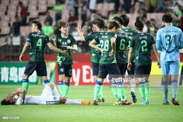 Supachok Sarachart of Buriram United shows dejection while Jeonbuk Hyundai Motors players celebrate their 20 victory and 43 aggregate win in the AFC...