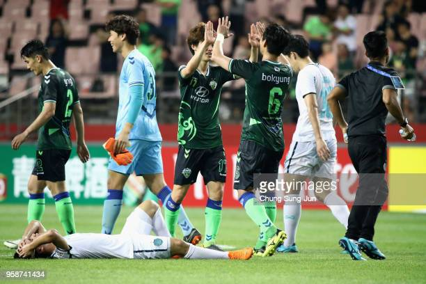 Supachok Sarachart of Buriram United shows dejection while Jeonbuk Hyundai Motors players celebrate their 1-0 victory and 4-3 aggregate win in the...