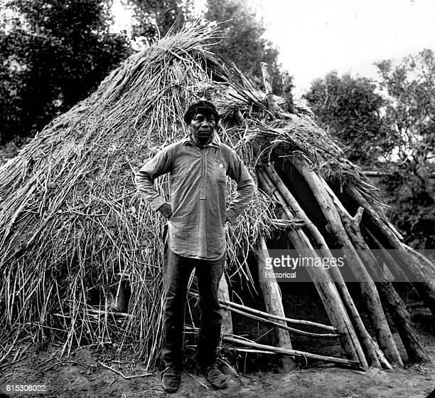 Supai Charlie a Havasupai man standing in front of his hawa a structure made of sticks and grass Havasu Canyon