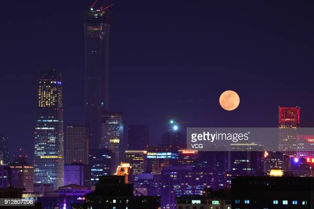 A Super Blood Moon rises over buildings on January 31 2018 in Beijing China The moon turns red and blue during a total lunar eclipse on Wednesday...
