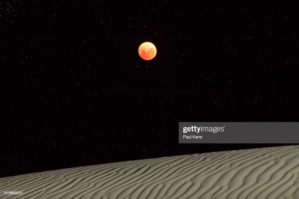 A Super Blue Blood Moon is seen over the sand dunes on January 31, 2018 in Lancelin, Australia. Last seen from Australia in December 1983, a Super Blue Blood Moon is the result of three lunar phenomena happening all at once. Not only is it the second full moon in January, but the moon will also be close to its nearest point to Earth on its orbit, and be totally eclipsed by the Earth's shadow.