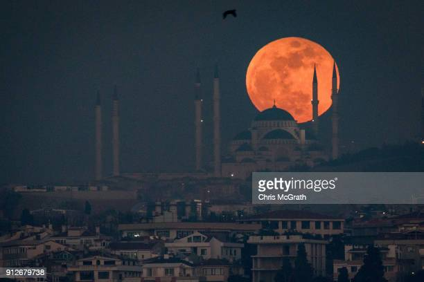 Super Blue Blood Moon rises behind the Camlica Mosque on January 31 2018 in Istanbul Turkey A Super Blue Blood Moon is the result of three lunar...