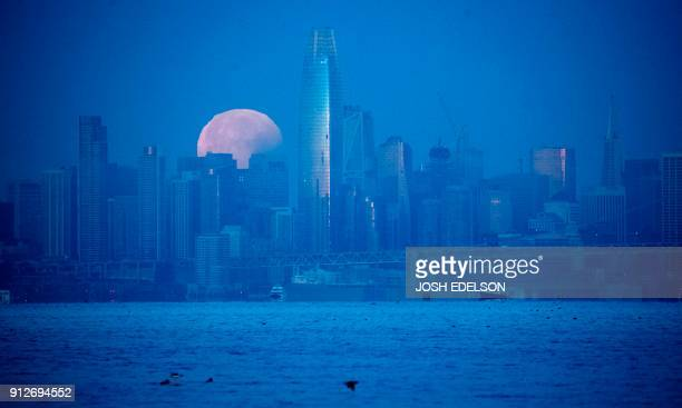 A super blue blood moon sets behind downtown San Francisco California before dawn on January 31 2018 For the first time in 35 years a blue moon...