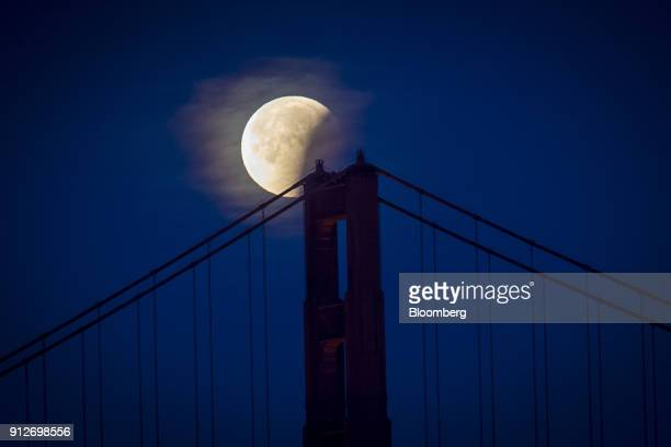 A super blue blood moon sets behind the Golden Gate Bridge in San Francisco California US on Wednesday Jan 31 2018 Blue moons are the second full...
