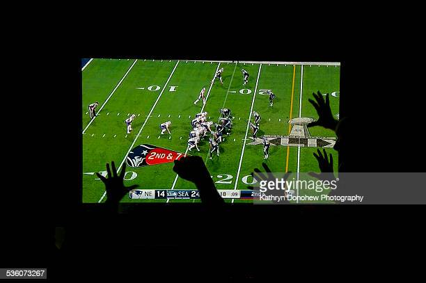 Super Bowl fans celebrate with cheering at a party Raised hands are silhouetted against a big screen TV
