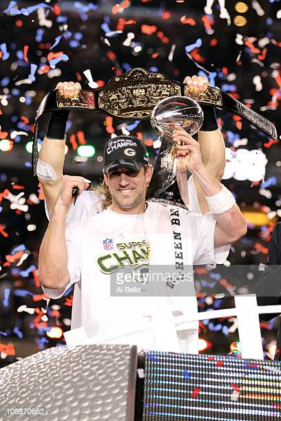 Super Bowl MVP Aaron Rodgers of the Green Bay Packers holds up the Vince Lombardi Trophy as Clay Matthews holds up a championship belt after winning...