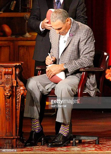 Former football coach Herm Edwards signs a football onstage during 'Feherty Live' at the Orpheum Theatre Phoenix Arizona