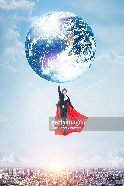 A super businessman flying with earth in his hand