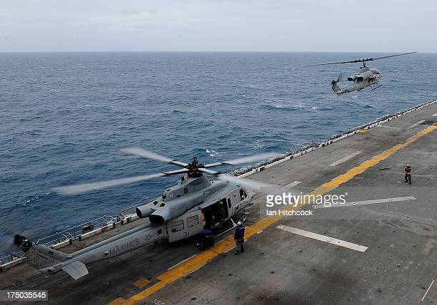 Super Cobra and a UH1Y Venom helicopter land on the deck of the USS Bonhomme Richard on July 30 2013 near Rockhampton Australia Over 30000 US and...