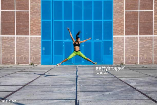 super fit woman exercising in city industrial district - determination and strength lead to success - industrial district stock pictures, royalty-free photos & images