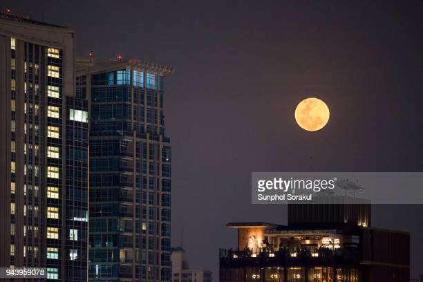 super full moon appears over bangkok skyscrapers - total lunar eclipse stock photos and pictures