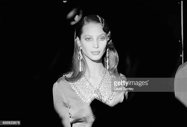 Super model Christy Turlington strolls off stage wearing huge earrings and jeweled collar