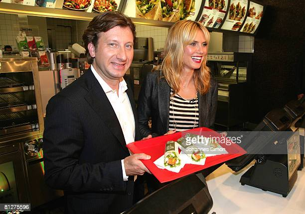 Super model Heidi Klum and Markus Pichler head of marketing McDonald's Germany pose with three new designed McDonald's chicken wraps during a press...