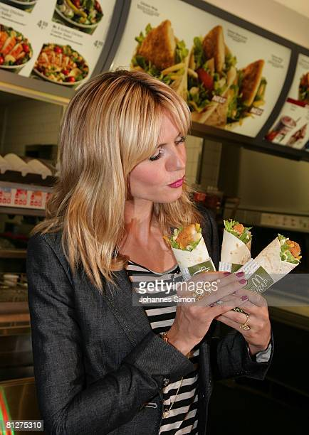 Super model Heidi Klum poses with three new designed McDonald's chicken wraps during a press conference at the Munich Inner City McDonald's...