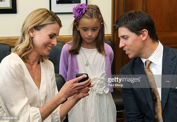 Super model Niki Taylor March of Dimes National Ambassador Nina Centofanti and NASCAR driver Denny Hamlin look at a few photos while waiting for the...