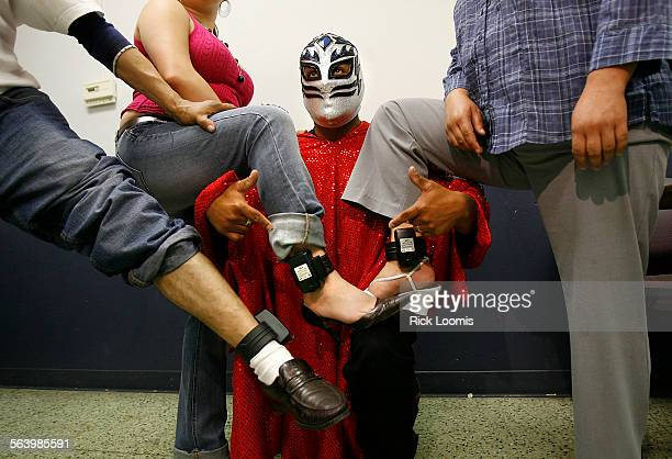 Super Mojado a wrestler fighting for the cause of undocumented immigrants poses with three people wearing GPS house arrest tracking ankle bracelets...
