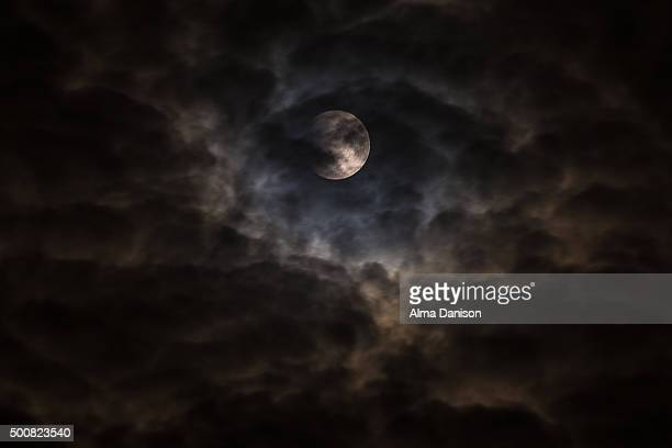 super moon behind clouds - alma danison stock photos and pictures