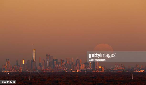 A super moon rises at sunset over lower Manhattan in New York City on November 13 2016 as seen from Watchung NJ