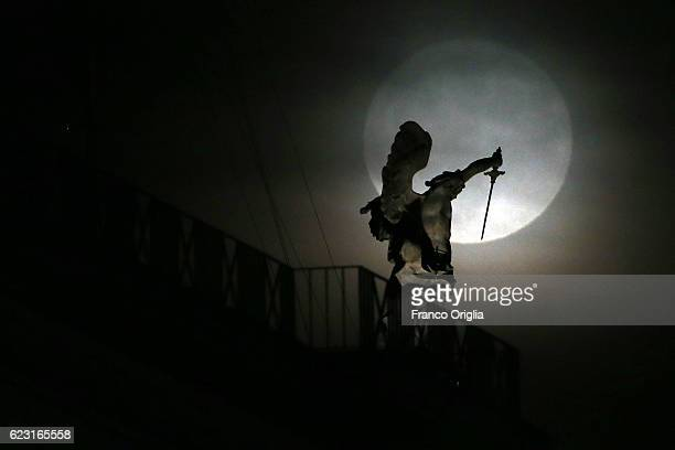 A super moon rises behind the bronze statue of Michael the Archangel standing on top of Castel Sant'Angelo on November 14 2016 in Rome Italy A...