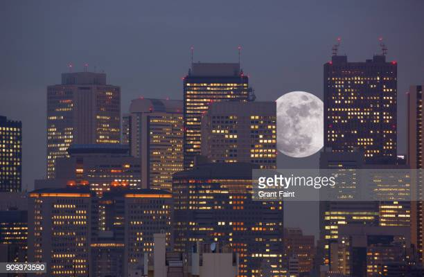 super moon rising between office towers - tokyo japan stock pictures, royalty-free photos & images