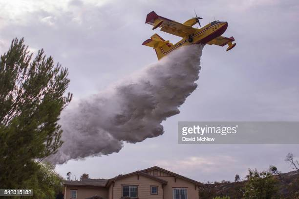 Super Scooper CL-415 firefighting aircraft from Canada makes a drop to protect a house during the La Tuna Fire on September 3, 2017 near Burbank,...