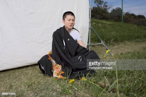 Super short hair young woman sitting on the wildness ground wearing ethnic costumes.
