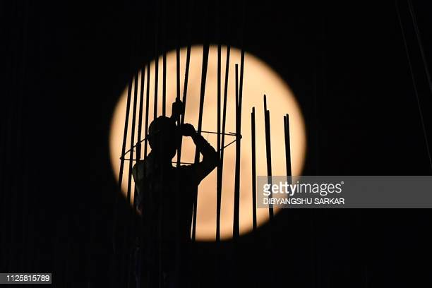 A 'Super Snow Moon' rises as an Indian construction labourer works at a building site in Kolkata on February 19 2019 Super Moon is a term used when a...