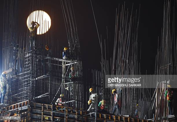 TOPSHOT A 'Super Snow Moon' rises as Indian construction labourers work at a building site in Kolkata on February 19 2019 Super Moon is a term used...