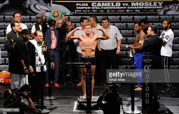 WBC super welterweight champion Canelo Alvarez poses on the scale as Shane Mosley looks on during the official weighin for their bout at the MGM...