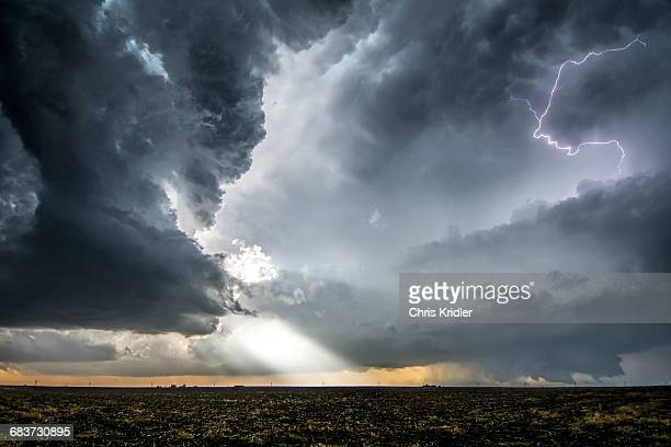 a supercell and tornado under the base of a storm, with beams of sunlight and lightning emerging from storm layers, dodge city, kansas - extreme weather stock pictures, royalty-free photos & images