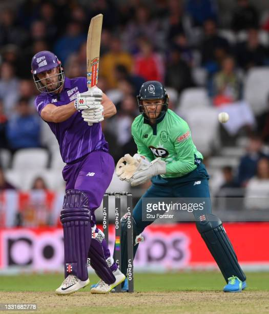 Superchargers batter Chris Lynn hits out watched by Sam Billings during The Hundred match between Northern Superchargers Men and Oval Invincibles Men...
