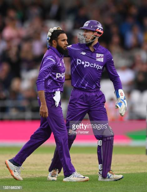 Superchargers bowler Adil Rashid is congratulated by John Simpson after taking the wicket of Laurie Evans during The Hundred match between Northern...